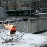 Soihtu rautalangasta tehdyn pallon sisällä lumisella betonilla.