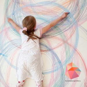 Tyttö piirtää seinälle isoja ympyröitä värikynillä.