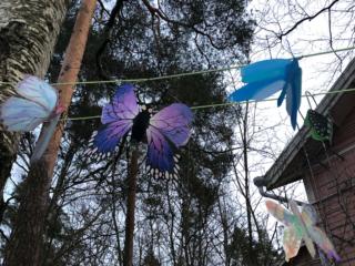 Keravan kuvataidekoulun pimeässä hohtavia hyönteisiä kuvataidekoulun pihapuihin ripustettuina.