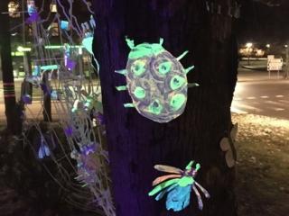 Keravan kuvataidekoulun pimeässä hohtavia hyönteisiä pihapuuhun ripustettuna.