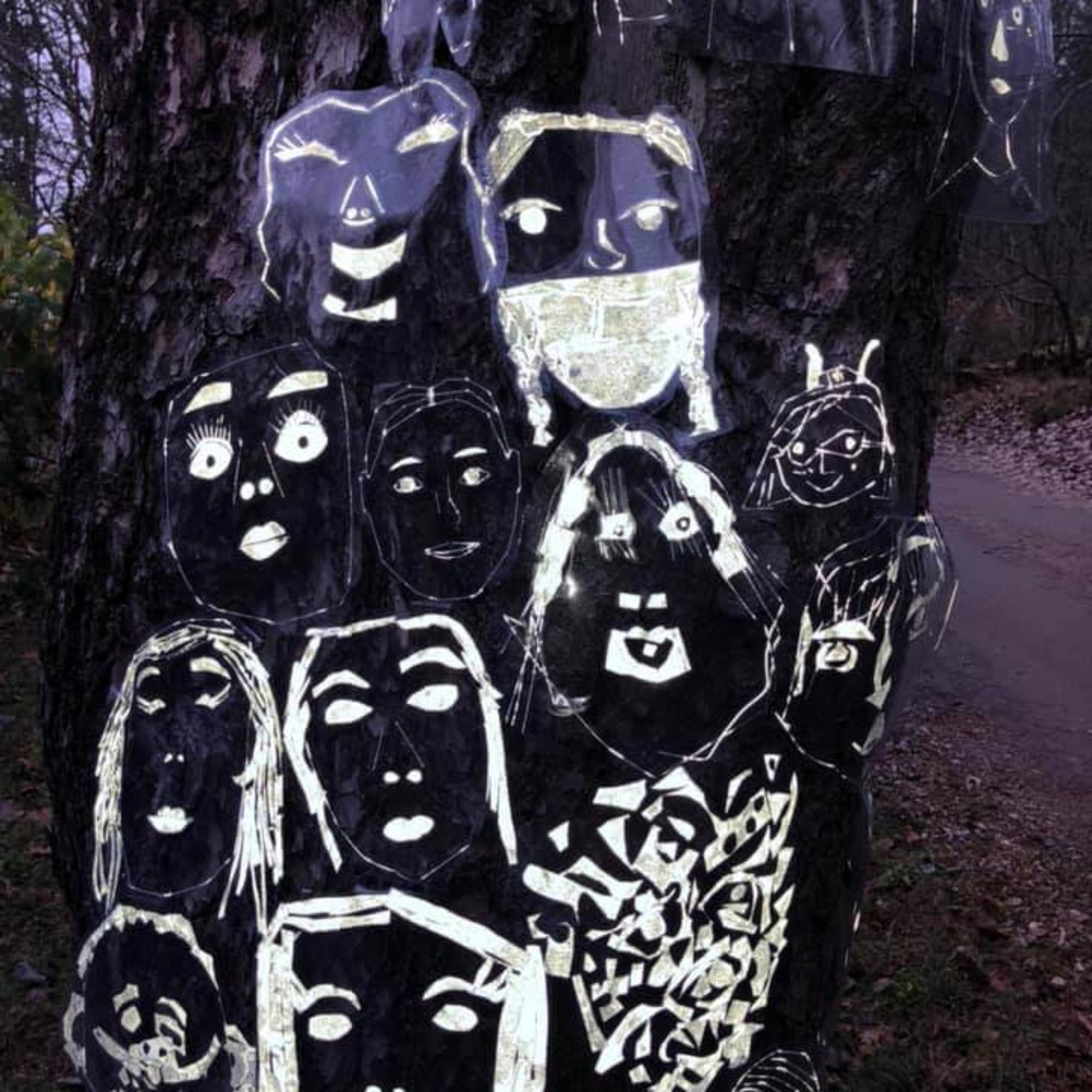 Kirkkonummen kuvataidekoulun oppilaiden heijastinkankaasta tekemiä kasvoja puun rungossa.