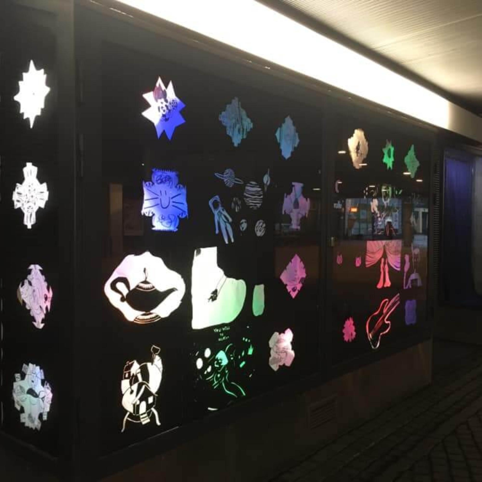 Kirkkonummen kuvataidekoulun Taikalyhty-valoteos Kauppakeskus Kirsikan alikulkutunnelin vitriinissä.