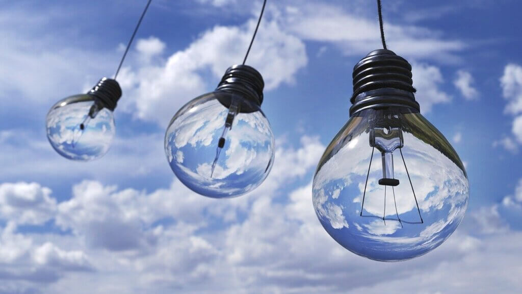 Kolme hehkulamppua poutapilvistä taivasta vasten.